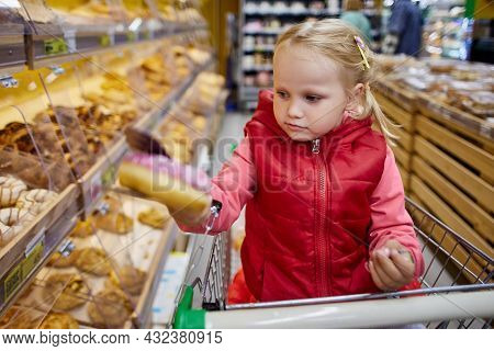 Little Girl Chooses Pastries In The Supermarket.