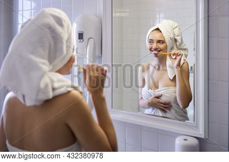 Woman Wrapped In Towel Brushes Her Teeth In Front Of Bathroom Mirror.
