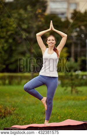 Yoga In Public Park, Young Woman In Her 30s Does Exercise By Placing Rug On Bench.