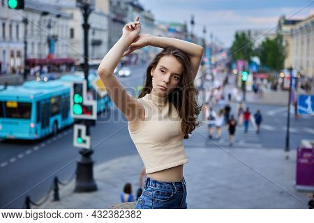Slender 18 Year Woman On Crowded City Street Of Summer Evening.