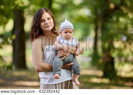 Young Mother With Nursing Baby In Her Arms In Public Park.