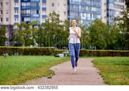 Woman In Her 20s Jogging In Multi Storey Area.