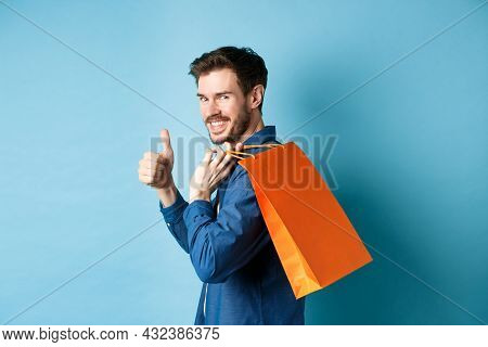Cheerful Shopper Holding Orange Shopping Bag On Shoulder, Turn Around At Camera With Thumbs Up, Reco