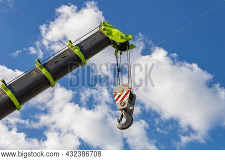 Telescopic Boom Of A Mobile Crane With A Hook Against A Cloudy Sky. Construction And Repair Equipmen