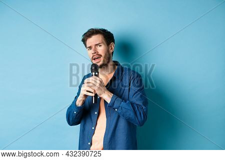 Young Man Singing Song In Microphone, Playing Karaoke, Standing On Blue Background
