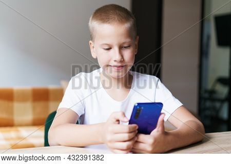Happy Cute Baby, Kid, Son Sitting At Table Relaxing, Having Fun With Mobile Phone, Playing Games, Wa