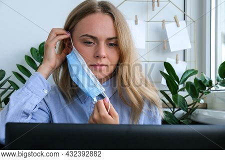 Young Woman Working On A Computer At Home. Business Woman Working On Her Laptop Wearing Medical Face