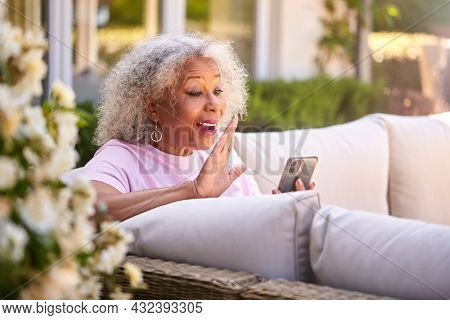 Senior Retired Woman Sitting Outside In Garden At Home Making Video Call On Mobile Phone