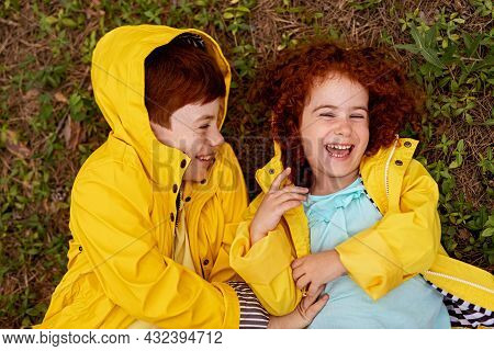 From Above Of Cheerful Little Redhead Sister And Brother In Similar Yellow Raincoats, Lying On Green