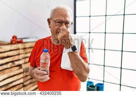 Senior man wearing sportswear and towel at the gym smelling something stinky and disgusting, intolerable smell, holding breath with fingers on nose. bad smell