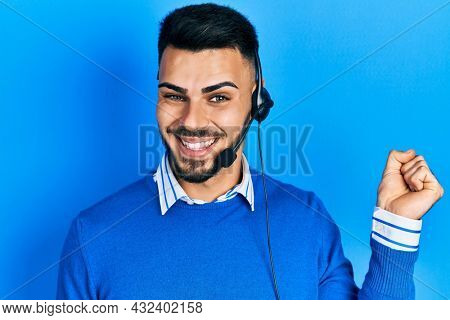 Young hispanic man with beard wearing operator headset at the call center office screaming proud, celebrating victory and success very excited with raised arm