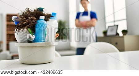 Young chinese housewife standing with arms crossed gesture and cleaning products on the table at home.