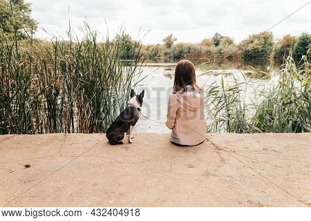 Little Girl Sitting With A Boston Terrier Dog On The Lakeshore - With Her Back Turned, Her Dog Stari