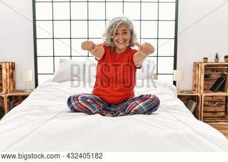 Middle age woman with grey hair sitting on the bed at home approving doing positive gesture with hand, thumbs up smiling and happy for success. winner gesture.