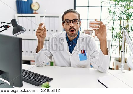 Young hispanic dentist man holding denture and toothbrush afraid and shocked with surprise and amazed expression, fear and excited face.