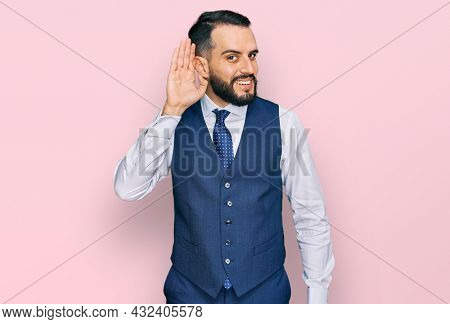Young man with beard wearing business vest smiling with hand over ear listening an hearing to rumor or gossip. deafness concept.