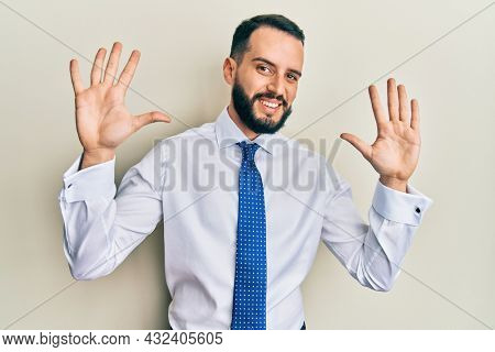 Young man with beard wearing business tie showing and pointing up with fingers number ten while smiling confident and happy.