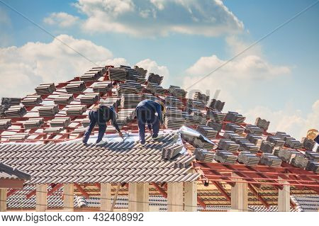 House Construction. Roofers Laying Tiles On The Roof Of New Building