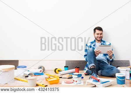 Smiling Caucasian Man Surfing Internet On Tablet Computer While Sitting Near Wall. House Remodeling