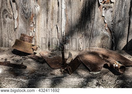 An Old Rusty Shovel And Other Metal Objects On A Wooden Shelf.