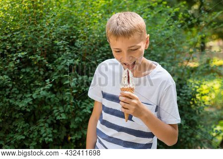 Teenager Boy Eating Ice-cream Cone On Green Nature Background. Summer, Junk Food And People Concept