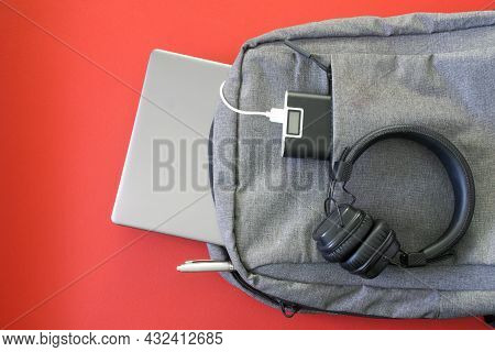 Modern Urban Backpack With Gadgets: Headphones, Laptop, Power Bank And Pen. Red Background. The Conc