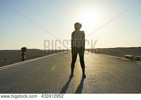 Asian Woman Backpacker Traveler Standing In The Middle Of A Road In Gobi Desert At Sunset