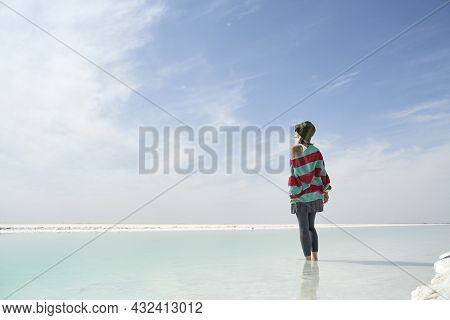 Asian Woman Standing In The Water Of A Salt Lake Looking At View