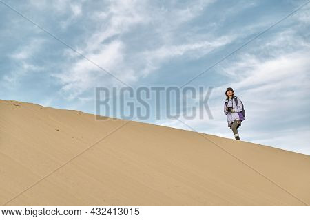 Asian Woman Photographer Walking On The Ridge Of A Sand Dune Looking At View