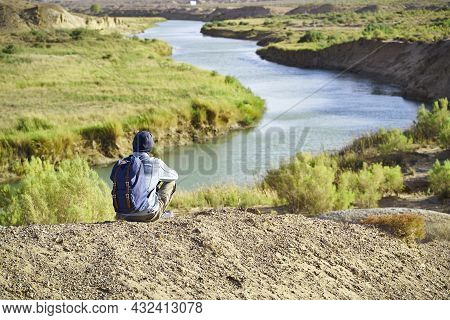 Rear View Of Male Asian Photographer Sitting On Top Of A Hill Looking Down At A River