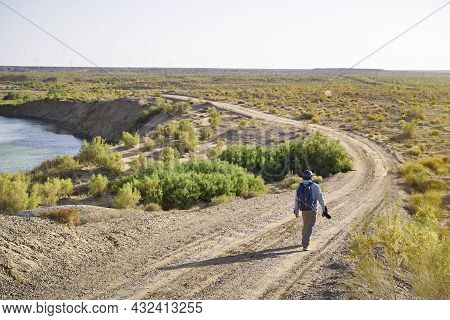 Asian Man Photographer Walking On Dirt Road In Gobi Desert Looking At Landscape At Sunset