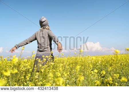 Rear View Of Asian Woman Tourist Embracing Nature In A Field Of Canola Flowers