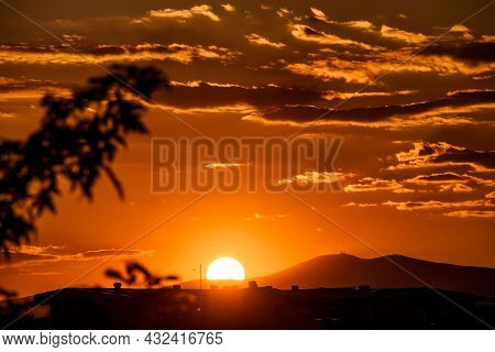 Fiery Sunset Over Rooftops And Far Away Hills In The Summer Time. Soft Focused Design Elements, Silh