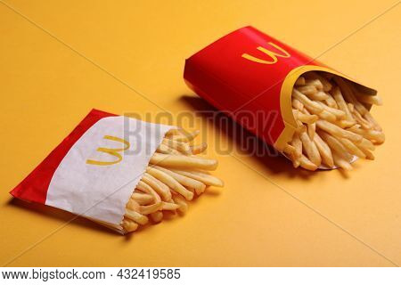 Mykolaiv, Ukraine - August 12, 2021: Small And Big Portions Of Mcdonald's French Fries On Orange Bac