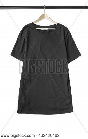 Black Basic T-shirt Hanging On Wooden Clothes Rack Isolated Over White