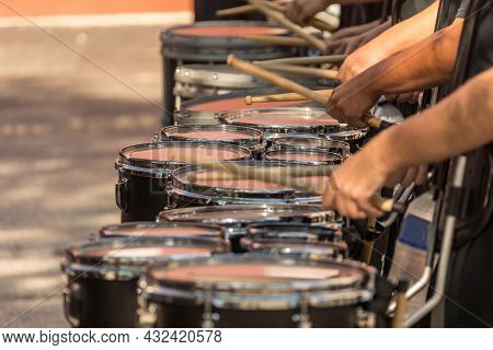 A Section Of A Marching Band Drum Line Warming Up For A Parade