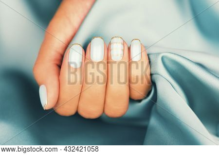 Beautiful Female Fingers With Blue Manicure And Sparkles. Colored French Manicure With Sparkles.