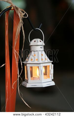 candle lantern hanging from a hook