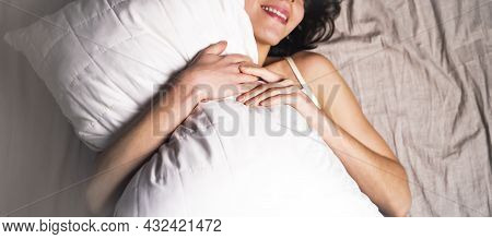 A Happy, Cute Girl With A Smile On Her Face Gently Hugs A White Soft Pillow, Lies In Bed And Feels C