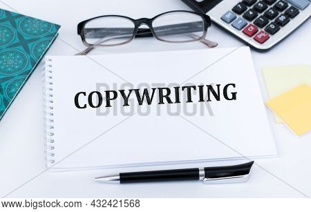 Copywriting Word On Open Notebook On Office Desk Near Pen, Glasses, Calculator
