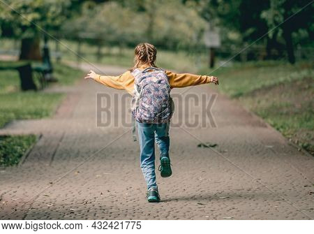 Preteen school girl with backpack running in the park after lessons portrait from back. Carefree child kid at autumn outdoors