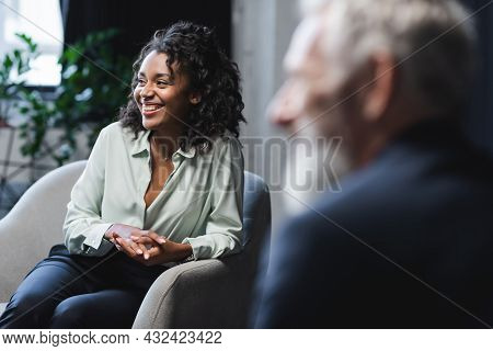 Cheerful African American Journalist Sitting In Armchair Near Blurred Guest