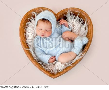Newborn baby boy sleeping wearing knitted costume and hat in tiny heart shape bed. Infant kid studio portrait with fur