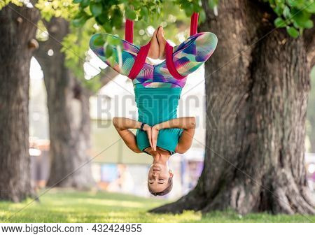 Sport girl practicing fly yoga in hammock at nature and stretching her back in the air. Young woman doing aero gymnastics and relaxing in summertime