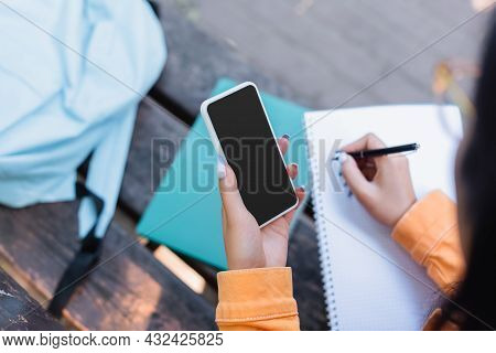 Partial View Of Student Writing In Notebook While Holding Smartphone With Blank Screen Outdoors