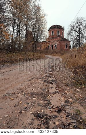 Autumn Country Road In An Abandoned Village Leading To An Old Dilapidated Church, Dry Plants And Bir