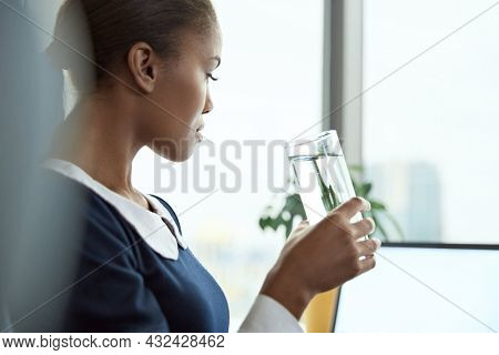 Concentrated african businesswoman drinking water and watching something on laptop computer in office. Concept of modern successful woman. Young black girl wearing formal clothes. Daytime