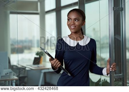 Smiling african businesswoman standing and holding laptop computer in modern office. Concept of successful woman. Young black girl wearing formal clothes. Daytime