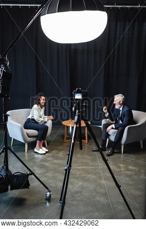 Happy African American Journalist Sitting In Armchair And Talking With Guest In Studio