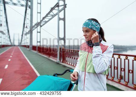 Young Woman Using Earbuds While Standing On The Bridge With A Baby Carriage, Ready For A Jog On A Cl